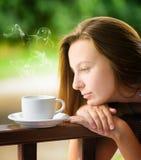 Cofee de consumición de la mujer joven en un jardín. Al aire libre retrato Imágenes de archivo libres de regalías