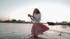 Cofee de la bebida de la mujer que mira en el puerto fluvial de salto y de baile de la puesta del sol almacen de video