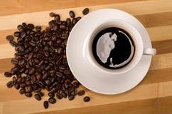 Cofee i kawowa fasola na drewnianej desce Zdjęcia Royalty Free