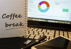 Cofee irrompe il blocco note sul posto di lavoro dell'ufficio Fotografie Stock Libere da Diritti