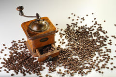 The Cofee. An old cofee grinder with coffe grain on a withe surface stock photo