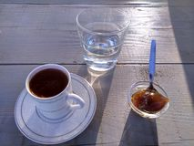 Cofee with water and sweet. Cup of cofee with sweet and water, in Greek morning light royalty free stock photography