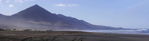 Cofete beach and dark volcanic mountains Stock Photos