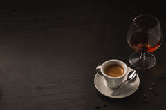 Coffè and cognac. Coffee and cognac on black wood table Royalty Free Stock Photography