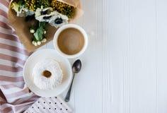 Coffe和一个多福饼与鲜花 免版税库存图片