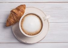 Coffe和新月形面包木背景早晨早餐顶视图cappuchino 免版税库存图片