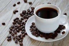 黑coffe和烤豆在一个白色杯子木表面上 免版税库存照片