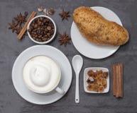 Coffe, ένα φλυτζάνι του καυτού latte ή cappuccino με το κουλούρι, τοπ άποψη Πιάτο υποβάθρου που γίνεται από τη φυσική πλάκα Φασόλ Στοκ φωτογραφίες με δικαίωμα ελεύθερης χρήσης