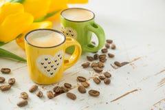 Coffe в зеленых и желтых чашках, тюльпанах Стоковая Фотография RF
