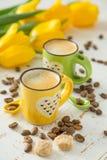 Coffe в зеленых и желтых чашках, тюльпанах Стоковое фото RF