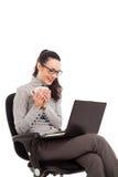 Coffe девушки брюнет выпивая, сидя в стуле с компьтер-книжкой стоковое фото