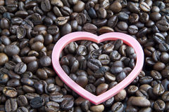 Pink heart on coffee beans Royalty Free Stock Photos