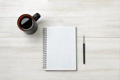 笔记本、杯子coffe和铅笔投入了桌 库存照片