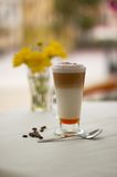 Coffe amaretto. Big caffe amaretto on the desk with flowers and white stock photography