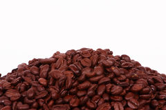 Coffe Bean Background. A pile of Columbian Coffee beans on the lower third of a white background Stock Photo