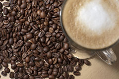 Coffe and beans 2. Coffee with froth and coffee beans below on the table stock photo