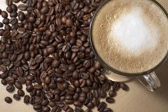 Coffe and beans. Coffee with froth and coffee beans below on the table. Lens focus on the glass stock image