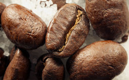 Coffe beans. A closeup of a few coffee beans on a bed of sugar Royalty Free Stock Images