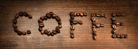 Coffe from coffe beans. Created words coffe on the textured wooden stock photo