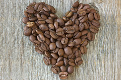 Coffe beans heart on wood background Royalty Free Stock Photos