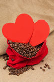 Coffe beans in red velvet sac with two red hearts Stock Images