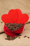 Coffe beans in red velvet sac with two red hearts Royalty Free Stock Photos
