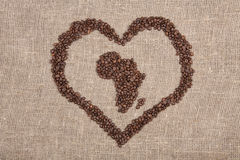Coffe beans shaping Africa with heart. On burlap Royalty Free Stock Images