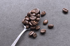 Coffe beans in steel spoon. S  on black Stock Photo