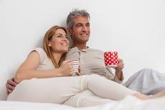Coffe bevente delle coppie felici nel letto Fotografia Stock