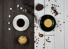 Coffe. Black coffee in a white cup and coffee with milk in a black cup on white and black backgrounds Stock Photos