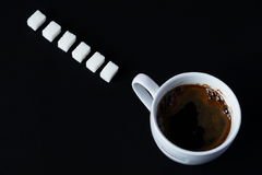 Coffe. Black coffee in a white cup and sugar pieces on a dark Royalty Free Stock Photo
