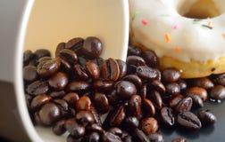 Coffe Bohnen und leeres Cup mit weißem Krapfen Stockfotografie