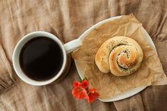 Coffe, broodje met papaverzaden en geraniumbloem stock afbeeldingen