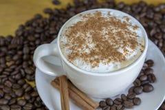 Coffe caldo con cannella con i chicchi di caffè arrostiti sulla parte posteriore di legno Fotografia Stock Libera da Diritti