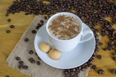 Coffe caldo con cannella con i chicchi di caffè arrostiti sulla parte posteriore di legno Fotografia Stock