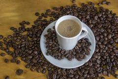 Coffe caldo con i chicchi di caffè arrostiti su fondo di legno Fotografia Stock Libera da Diritti