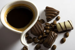 Coffe and chocolate. Coffee cup and chocolate candies on white background Stock Images