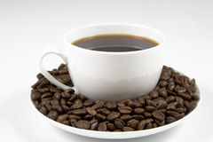Coffe cup of beans. White coffee cup full of coffee beans Stock Photo