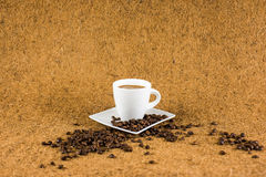 Coffe cup on brown background texture. With coffe beans Stock Images