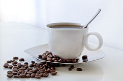 Coffe cup and coffe beans on a table Royalty Free Stock Image