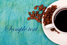 Coffe in cup with coffee beans around it Stock Photography