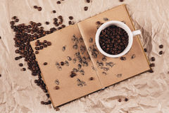 Coffe cup with coffee beans on book Stock Photography