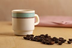 Coffe cup with coffee beans wooden table royalty free stock images