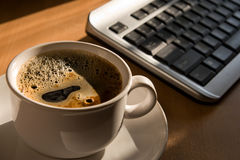 Coffe cup and keyboard on the office table. In the morning sun royalty free stock photos