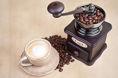 Coffe cup with wooden grinder. Royalty Free Stock Images