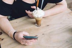 Coffe de consumición del hielo de la muchacha y el mandar un SMS en su teléfono que se sienta en la madera Foto de archivo libre de regalías