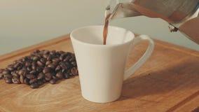 Coffe de derramamento no copo branco do geyser do café filme