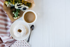 Coffe and a donut with fresh flowers Royalty Free Stock Images