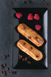 Coffe eclair with raspberries. Black squate plate with Coffe eclairs with fresh raspberries and coffee beans on black slate board. Top view Stock Image