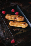 Coffe eclair with raspberries. Black squate plate with Coffe eclairs with fresh raspberries and coffee beans on wooden surface with dark palm bark. Top view Royalty Free Stock Photos